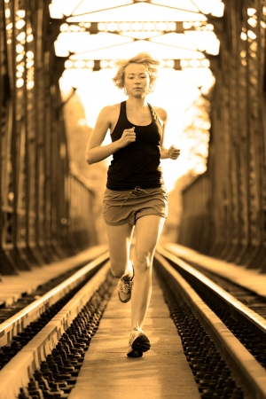 Athlete running on railaway tracks bridge in morning sunrise training for marathon and fitness. Healthy sporty caucasian woman exercising in urban environment before going to work; Active urban lifestyle. photo