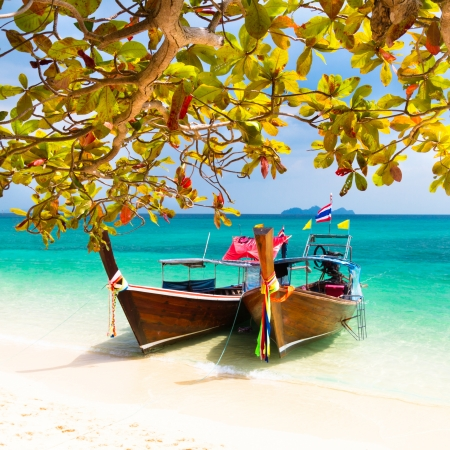 Traditional wooden long tail boats on a picture perfect tropical beach near Phuket, Thailand, Asia. photo