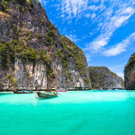 phi phi island: Traditional wooden  boat in a picture perfect tropical bay on Koh Phi Phi Island, Thailand, Asia  Stock Photo