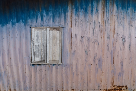 asbestos: Old rusty house with closed wooden shutters; can be used as a graphical background