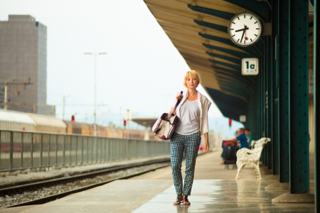Blonde caucasian woman waiting at the railway station carrying bag. photo