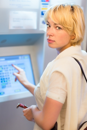 automatic machine: Lady buying a railway ticket at the automatic ticket vending machine with touch screen. Stock Photo