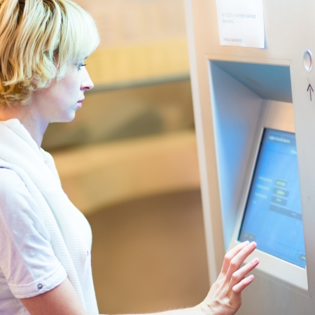 automatic teller machine bank: Lady buying a railway ticket at the automatic ticket vending machine with touch screen. Stock Photo