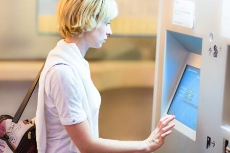 Lady achat d'un billet de chemin de fer au distributeur automatique de billets avec écran tactile.