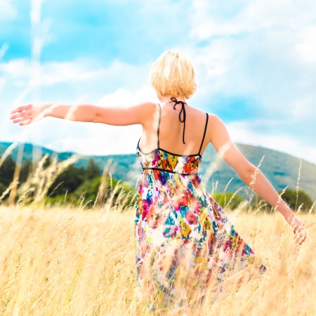 Lady enjoying the nature  Young woman arms raised enjoying the fresh air in summer meadow  photo