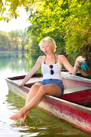 soaking: Carefree young blonde woman enjoying the sunny summer day on a vintage wooden boats soaking her feet  in cold lake in pure natural environment on the countryside.