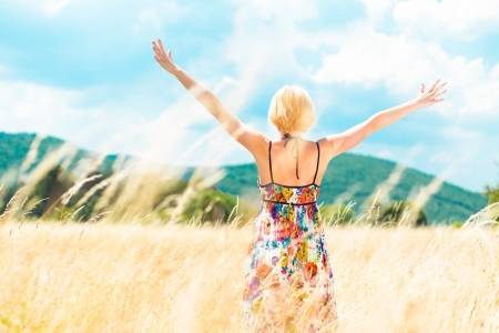 Lady enjoying the nature. Young woman arms raised enjoying the fresh air in summer meadow. photo