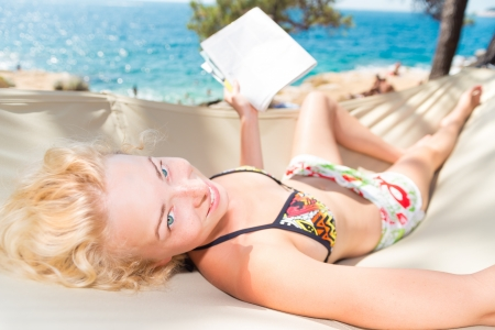 Beautiful girl lies on hammock on the beach and reads the magazine. photo
