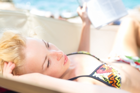Thoughtful woman  lying on hammock on the mediterranean beach while reading the book. photo