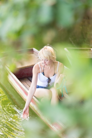 Thoughtful young blonde woman enjoying the sunny summer day on a vintage wooden boats on a lake in pure natural environment on the countryside. photo