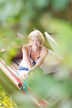 Carefree young blonde woman enjoying the sunny summer day on a vintage wooden boats on a lake in pure natural environment on the countryside. photo