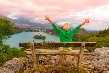 bled: Traveler arms rised enjoying the sunset panoramic view of  Julian Alps, Lake Bled with St. Marys Church of the Assumption on the small island; Bled, Slovenia, Europe. Stock Photo