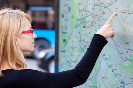 woman stop: Woman orientating herself on the public transport map.