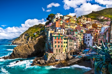 Riomaggiore fisherman village in a dramatic windy weather. Riomaggiore is one of five famous colorful villages of Cinque Terre in Italy, suspended between sea and land on sheer cliffs upon the  turquoise sea. photo