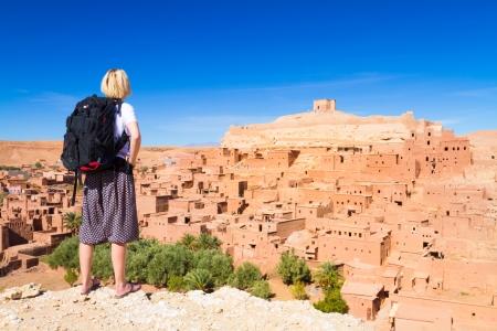 desierto del sahara: Mujer Aventurero mirando Ait Ben Haddou, ciudad fortificada, kasbah o ksar, a lo largo de la antigua ruta de caravanas entre el Sahara y Marrakech, en la actual Marruecos.