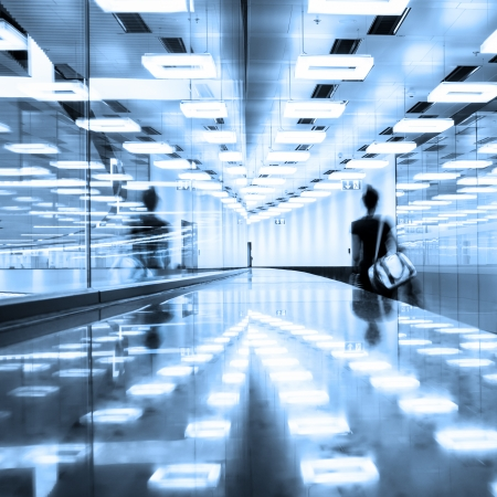 illuminated: Blurred silhouette of a traveler walking down the contemporary illuminated airport terminal corridor.