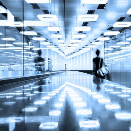 iluminados: Borrosa silueta de un viajero caminando por el pasillo terminal del aeropuerto iluminado contemporáneo. Foto de archivo