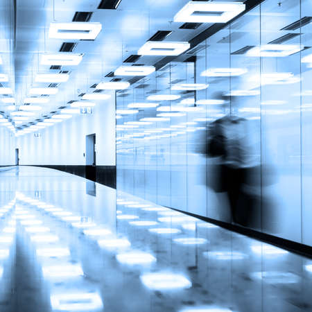 Blurred silhouette of a business traveler  walking along contemporary illuminated airport terminal hall. photo