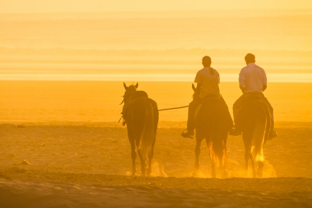 Man horse riding on the beach at sunset. photo