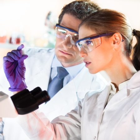 microscope slide: Attractive young scientist and her suprvisor looking at the microscope slide in the forensic laboratory.