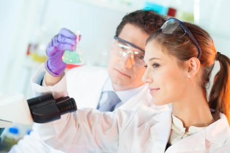 lab tech: Chemical laboratory scene: attractive young student and her post doctoral supervisor scientist observing the green indikator solution color shift in glass flask.