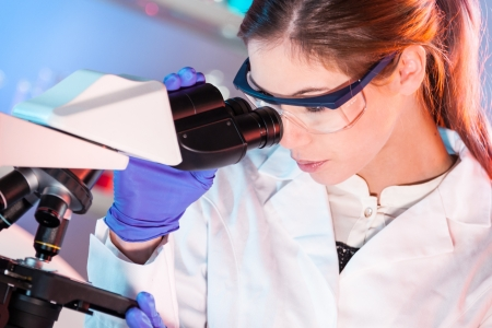 microscope slide: Attractive young scientist looking at the microscope slide in the forensic laboratory.