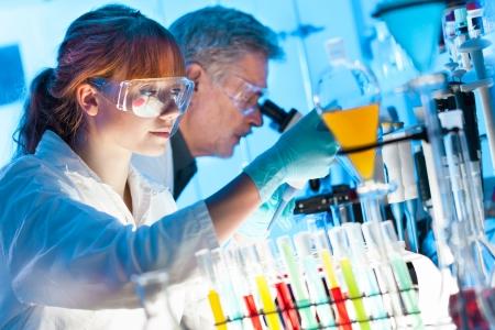 Aantrekkelijke jonge vrouwelijke wetenschapper en haar senior mannelijke begeleider pipetteren en microscopeerkleurstoffen in de life science research laboratorium biochemie, genetica, forensisch onderzoek, microbiologie
