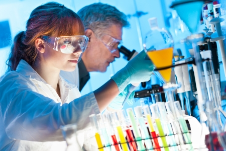 Attractive young female scientist and her senior male supervisor pipetting and microscoping in the life science research laboratory  biochemistry, genetics, forensics, microbiology Stok Fotoğraf - 24372384