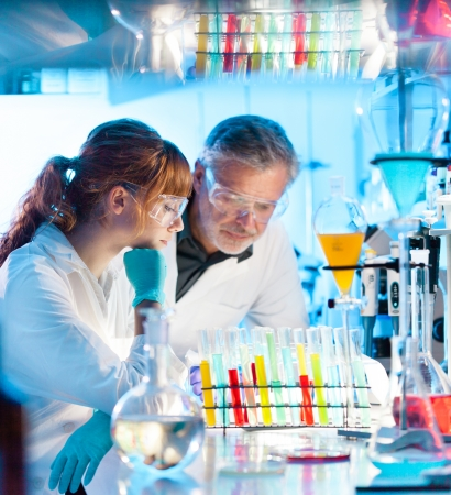 Attractive young female scientist and her senior male supervisor looking at the cell colony grown in the petri dish in the life science research laboratory  bichemistry, genetics, forensics, microbiology Stock Photo - 24372388