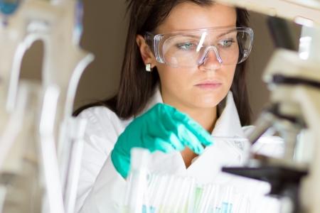 Escena de laboratorio químico científico atractivo joven estudiante de doctorado observando el indicador azul cambio de color después de la destilación solución