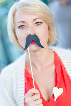 comedy disguise: Portrait of girl wearing fake mustache  symbol of Movember, annual, month-long event involving the growing of moustaches during the month of November to raise awareness of men