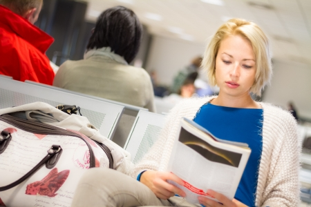 Casual blond young woman reading a magazine while waiting to board a plane at the departure gates. Stock Photo