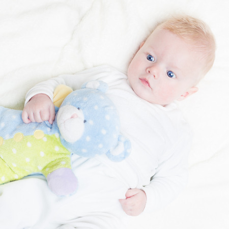 Cute blonde little baby boy with blue eyes with his favorite plush teddy bear and elephant. photo
