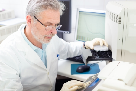 Life science researcher  performing a genotyping testing which enables personalized medicine. PM is a medical model that proposes the customization of healthcare. photo