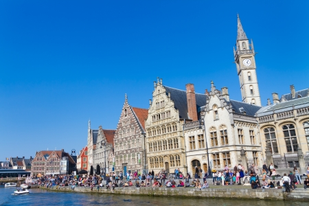 GHENT, BELGIUM - 21 APRIL : Picturesque medieval buildings overlooking the 'Graslei harbor' on Leie river in Ghent, Belgium on 21 April 2013. People gathered on the banks of the river Leie enjoy a sunny Sunday afternoon.