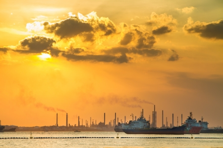 tanker ship: Industrial ships in front of refinery and heavy industry in the sunset. Environment pollution issue.