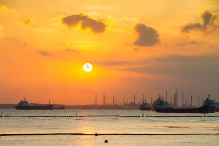 pollutant: Industrial ships in front of refinery and heavy industry in the sunset. Environment pollution issue.