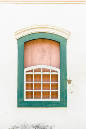 colonial: Decorative, colonial, green, vintage, window on a white wall in Paraty (or Parati), Brazil.