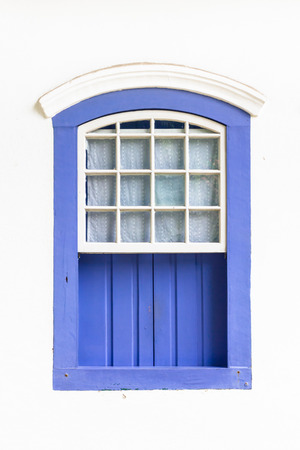 Decorative, colonial, blue, vintage, window on a white wall in Paraty (or Parati), Brazil. photo
