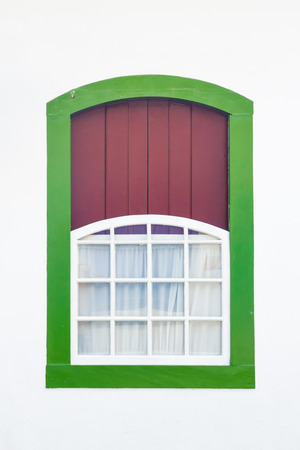 Decorative, colonial, green, vintage, window on a white wall in Paraty (or Parati), Brazil. photo