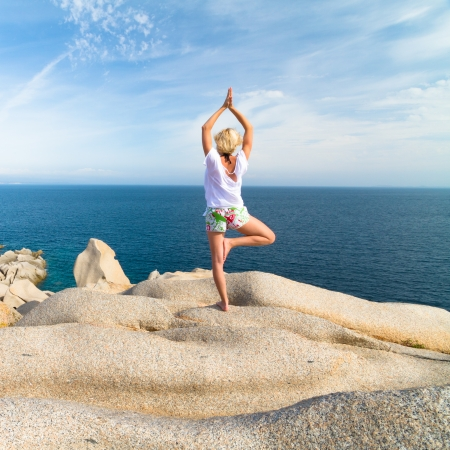 Sporty active woman practicing yoga at the beach. photo