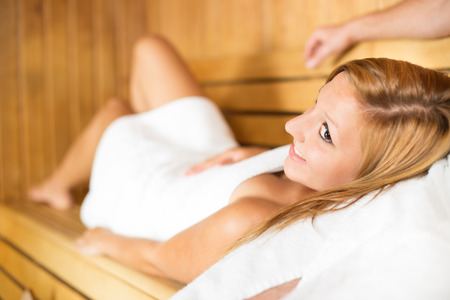 sweat girl: Young beautiful lady relaxing in traditional wooden Finnish sauna.