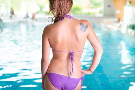 butterfly tattoo: Joven mujer sexy por una piscina cubierta.