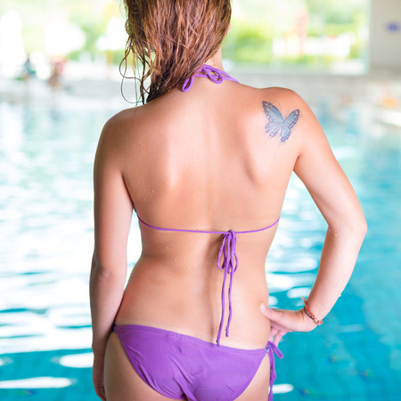 farfalla tatuaggio: Giovane signora sexy da piscina coperta. Archivio Fotografico