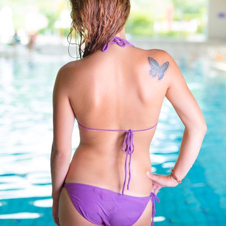 mojado: Joven mujer sexy por una piscina cubierta.