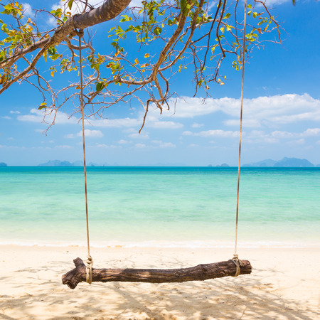 dyllic: Swing on dyllic crystal clean tropical beach with coral reef. Stock Photo