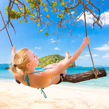 Lady swinging on the picture perfect tropical beach with the view of the island and turquoise coral reef on a sunny summer day. photo