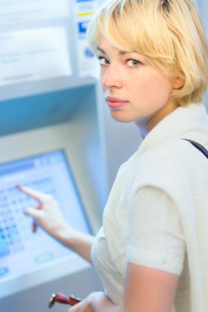 automatic transaction machine: Señora de comprar un billete de tren en la máquina expendedora de boletos automático con pantalla táctil.