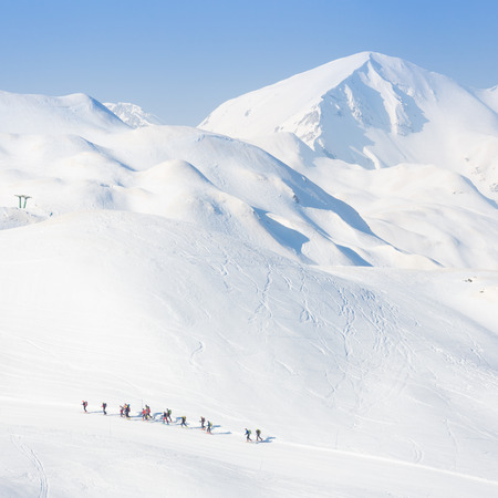 adventure holiday: Group of touring skiers on the ski slopes in Alps, Vogel, Slovenia, Europe.