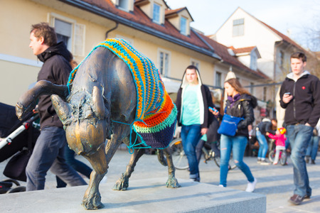 Artistic detail on a dog sculpture in medieval city center of Ljubljana, Slovenia, Europe. Lively terracing atmosphere can be seen in the background. People enjoying in the first spring sun. photo